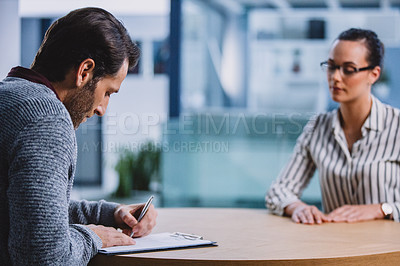 Buy stock photo Cropped shot of a handsome mature businessman sitting with a female colleague and signing a contract after a successful interview