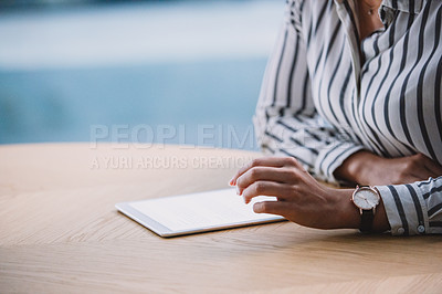 Buy stock photo Cropped shot of an unrecognizable businesswoman sitting alone in her office and using a tablet