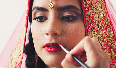 Buy stock photo Studio shot of a beautiful young woman getting her makeup done on her wedding day