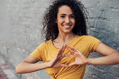 Buy stock photo Cropped portrait of an attractive young woman standing alone outside and making a heart sign gesture against a gray background