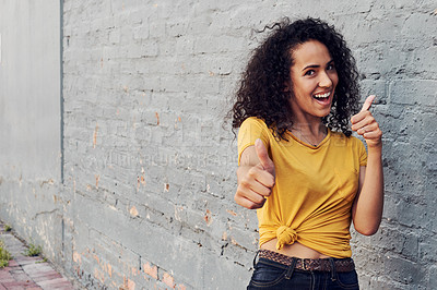 Buy stock photo Cropped portrait of an attractive young woman standing outside alone and making a thumbs up gesture against a gray background