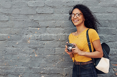 Buy stock photo Cropped shot of an attractive young woman standing alone outside against a gray background and holding a camera