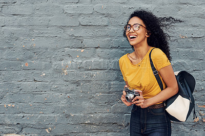 Buy stock photo Cropped shot of an attractive young woman holding a camera and standing alone against a gray background