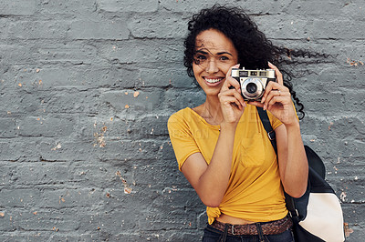 Buy stock photo Cropped portrait of an attractive young woman holding a camera and taking a picture while standing against a gray background