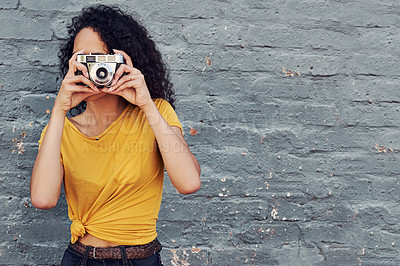 Buy stock photo Cropped shot of an attractive young woman holding a camera and taking a picture while standing against a gray background