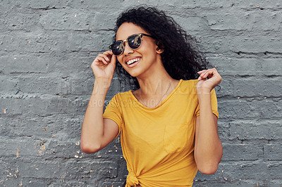 Buy stock photo Cropped shot of an attractive young woman wearing sunglasses and smiling while standing against a gray background outdoors