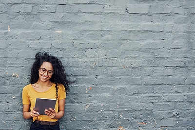 Buy stock photo Cropped shot of an attractive young woman using a tablet and standing alone against a gray background