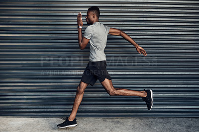 Buy stock photo Shot of a sporty young man running against a grey background