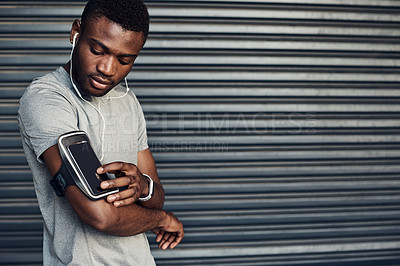 Buy stock photo Shot of a sporty young man listening to music while exercising against a grey background