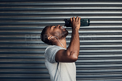 Buy stock photo Shot of a sporty young man drinking water while exercising against a grey background