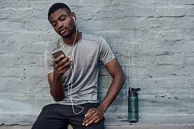 Buy stock photo Shot of a sporty young man wearing earphones while using a cellphone against a grey wall