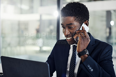 Buy stock photo Shot of a young businessman talking on a cellphone while working on a laptop in an office