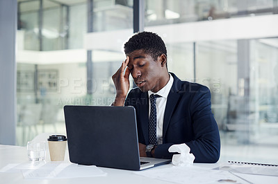 Buy stock photo Shot of a young businessman looking unwell while working on a laptop in an office