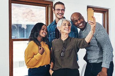 Buy stock photo Cropped shot of a group of cheerful businesspeople taking a self portrait together with a cellphone inside of the office