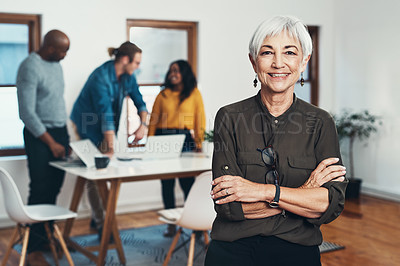 Buy stock photo Portrait of a cheerful mature businesswoman standing with her arms folded and her work colleagues in the background inside of the office