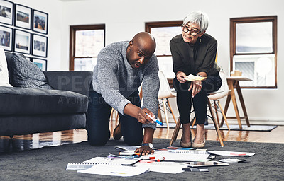 Buy stock photo Full length shot of two businesspeople looking over paperwork while working on the floor of their office