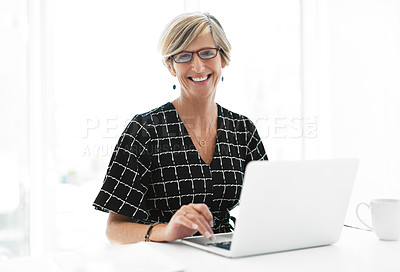 Buy stock photo Cropped portrait of an attractive mature businesswoman smiling while working on a laptop in her office