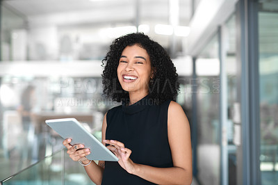 Buy stock photo Cropped portrait of an attractive young businesswoman laughing while using a digital tablet in a modern office