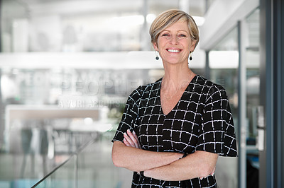 Buy stock photo Cropped portrait of an attractive mature businesswoman standing with her arms crossed in a modern office