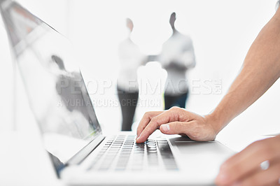 Buy stock photo Cropped shot of an unrecognizable businessman using a laptop with his colleagues in the background