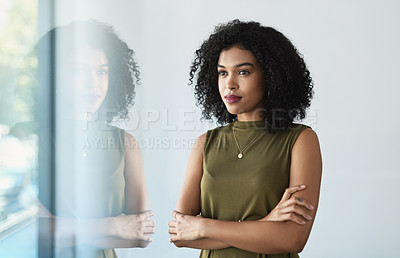 Buy stock photo Cropped shot of an attractive young businesswoman standing with her arms crossed in a modern office