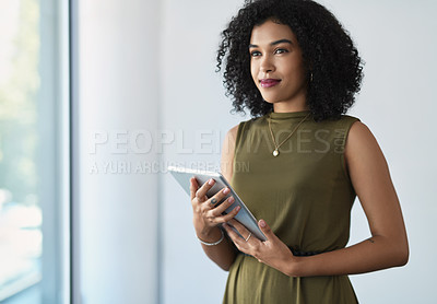 Buy stock photo Cropped shot of an attractive young businesswoman holding a digital tablet while standing in a modern office