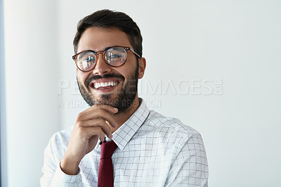 Buy stock photo Cropped portrait of a handsome young businessman standing with his hand on his chin in a modern office
