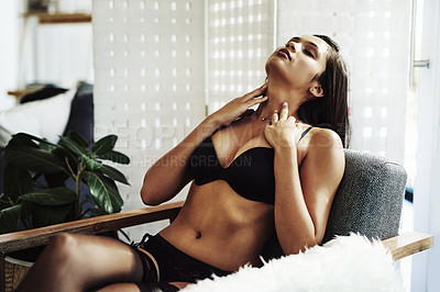 Buy stock photo Cropped shot of an attractive young woman sitting in a chair in her bedroom while wearing lingerie