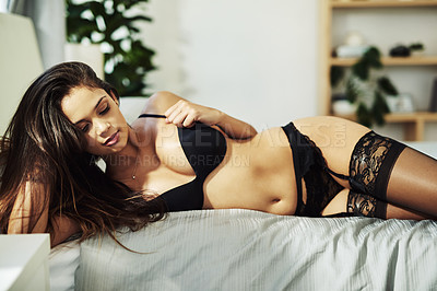 Buy stock photo Cropped shot of an attractive young woman posing seductively on her bed while wearing lingerie