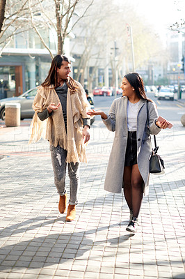Buy stock photo Full length shot of two affectionate young friends having a discussion while walking in the city