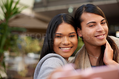 Buy stock photo Cropped shot of two affectionate young friends taking a selfie together outdoors