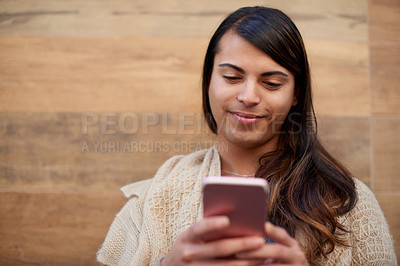 Buy stock photo Cropped shot of a young gender fluid person using a smartphone while standing outdoors