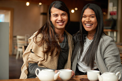 Buy stock photo Cropped shot of two affectionate young friends smiling while sitting together in a coffee shop