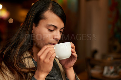 Buy stock photo Cropped shot of a young gender fluid person sipping a cup of a coffee in a cafe