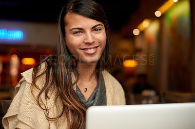 Buy stock photo Cropped portrait of a young gender fluid person smiling while using a laptop in a cafe