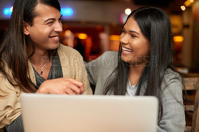 Buy stock photo Cropped shot of two affectionate young friends laughing while using a laptop together in a coffee shop
