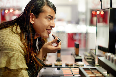 Buy stock photo Cropped shot of a young gender fluid person trying on lipstick in a cosmetics shop