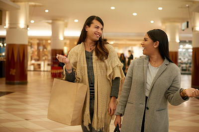 Buy stock photo Cropped shot of two affectionate young friends smiling at each other while walking through a shopping mall