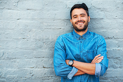 Buy stock photo Cropped portrait of a handsome young man smiling while standing with his arms crossed against a brick wall