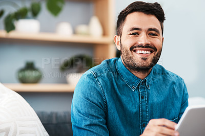 Buy stock photo Cropped portrait of a handsome young man smiling while holding a digital tablet in his living room at home