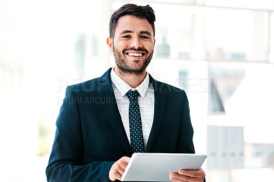 Buy stock photo Cropped portrait of a handsome young businessman smiling while holding a digital tablet in a modern office