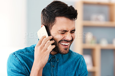 Buy stock photo Cropped shot of a handsome young man laughing while taking a phonecall in his living room at home