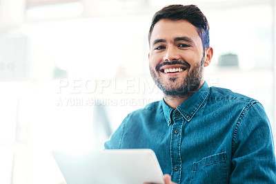 Buy stock photo Cropped portrait of a handsome young businessman smiling while holding a digital tablet in an office