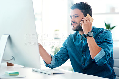 Buy stock photo Cropped shot of a handsome young businessman looking at a computer while taking a phonecall in an office