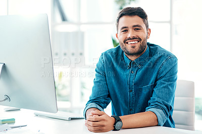 Buy stock photo Cropped portrait of a handsome young businessman smiling while sitting at his desk in a modern office