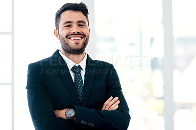 Buy stock photo Cropped portrait of a handsome young businessman smiling while standing with his arms crossed in a modern office