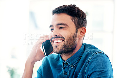Buy stock photo Cropped shot of a handsome young businessman smiling while taking a phonecall in an office