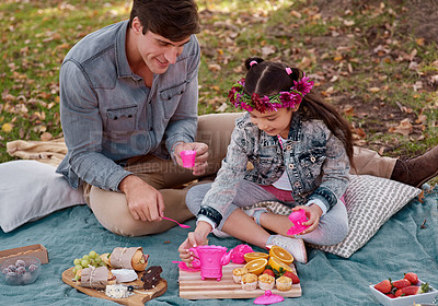Buy stock photo Shot of an adorable little girl having a tea party in the park with her father