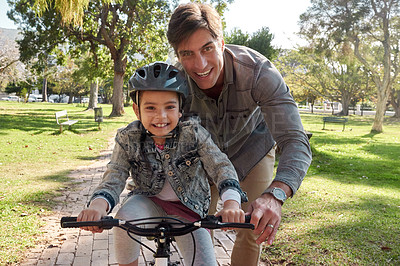 Buy stock photo Shot of an adorable little girl learning to ride a bicycle with her father in the park