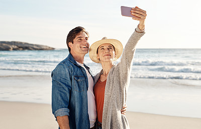 Buy stock photo Cropped shot of a middle aged couple taking a selfie on the beach